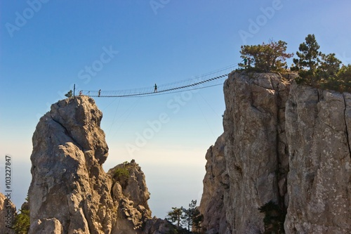 People crossing the chasm on the hanging bridge Fototapet