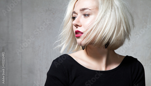 Fotografia Close-up portrait of a beautiful blonde with red lips on a black background