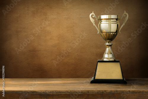 Fotografia champion golden trophy on wood table with blackboard copy space