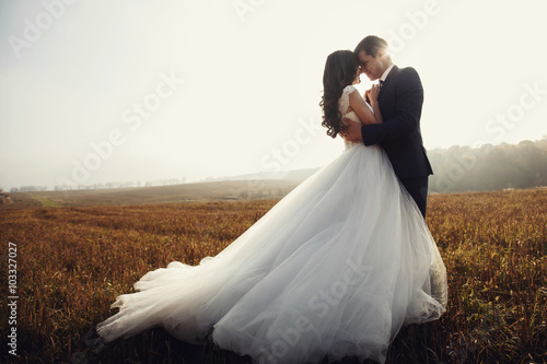 Obraz na plátne Romantic fairytale newlywed couple hug & kiss in field at sunset