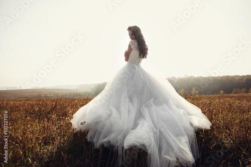 Murais de parede Beautiful happy brunette bride in white dress posing in sunset f