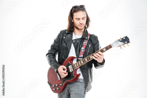 Fototapeta Serious young male guitarist standing and playing electric guitar