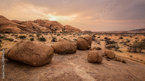 Fotografie, Obraz Typical round stones in the Namibian savanna at sunset