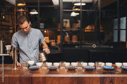 Barista preparing coffee tasting with rows of cups and beans Fototapeta