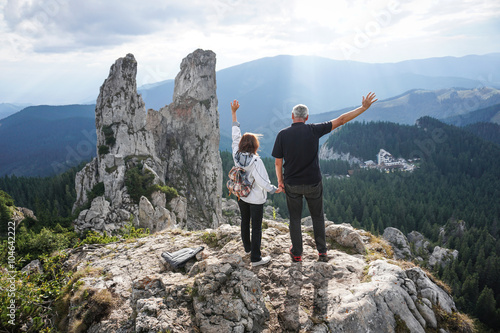 Elderly couple using a laptop on top of a mountain фототапет