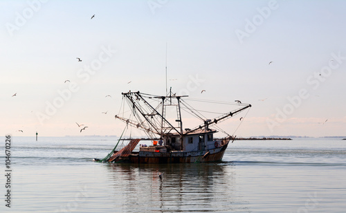 Fotografiet Commercial Fishing Boat/Commercial fishing boat enters the harbor at sunset