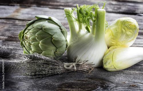 vegetable still life - fresh artichoke, fennel, endives and thyme on genuine wood background for home-made vegetarian cooking, studio shot