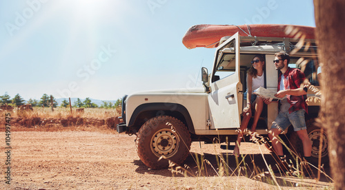 Young couple on road trip reading map for directions