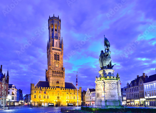Obraz na płótnie Belfry tower and a heroic statue in the town square of Brugge illuminated at dus