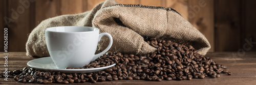 Fotografia still life with coffee beans and cup on the wooden background