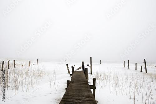 Pier in fog in the winter