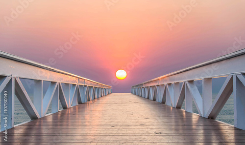 The bridge leads to the sea during sunset.