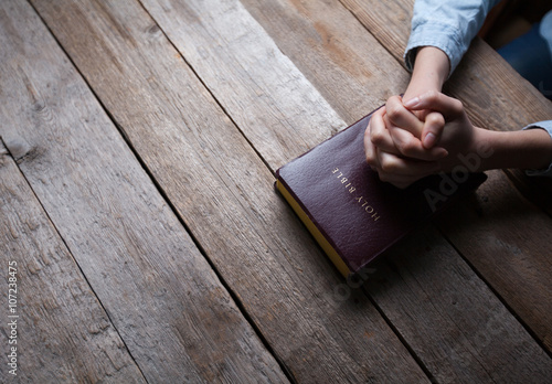 Fotografia hands praying with a bible in a dark over wooden table
