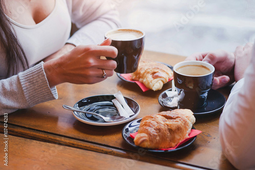 Vászonkép coffee and croissants in cafe, hands of couple closeup