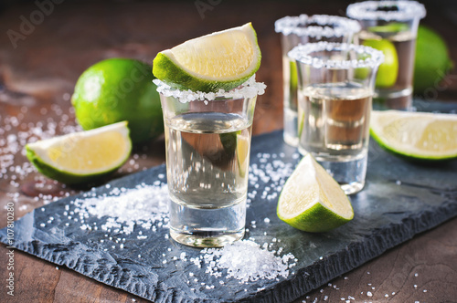 Fotografia Tequila gold, Mexican, alcohol in shot glasses, lime and salt, toned image, sele