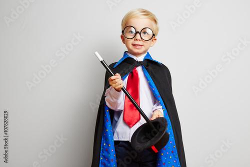 Photographie Kind zeigt Kunststück als Zauberer