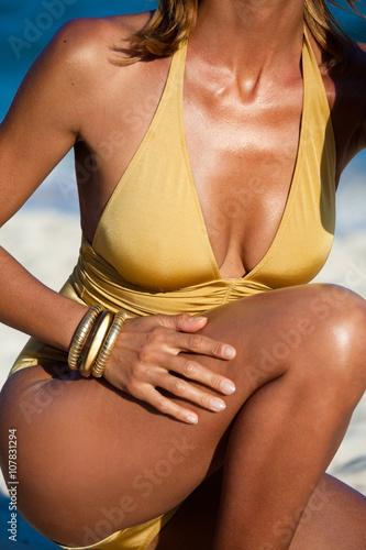 Foto corps de femme à la plage en maillot de bain doré