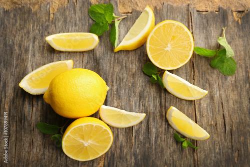 Slices of fresh lemons on wooden background
