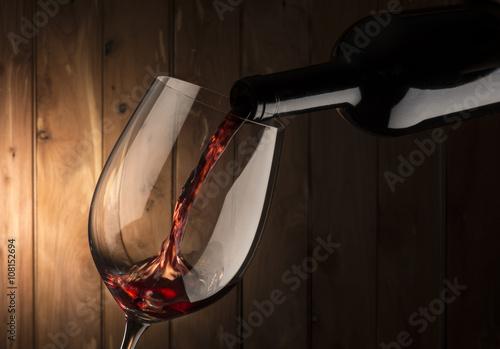 Obraz na plátně Sklo s červeným vínem na dřevěném pozadí