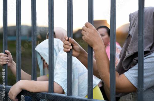 Obraz na płótnie Refugee peoples hand holding metal bar on refugee camp site  sit