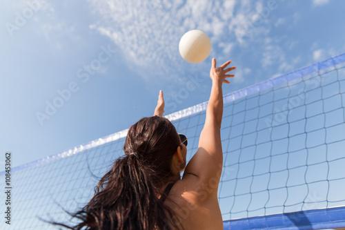 Obraz na plátně Mladá žena s míčem hrát volejbal na pláži