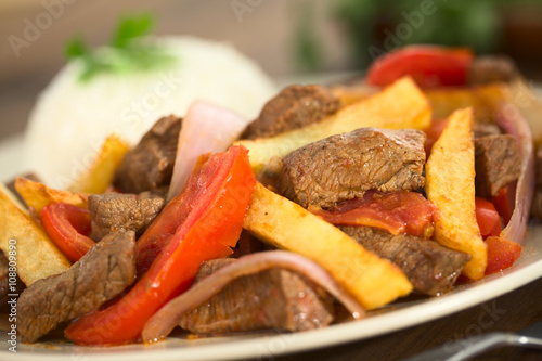 Peruvian dish called Lomo Saltado made of beef, tomato, red onion and French fries, served with rice (Selective Focus, Focus one third into the dish)