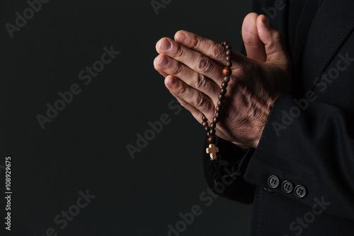 Obraz na plátne Hands of priest holding rosary and praying