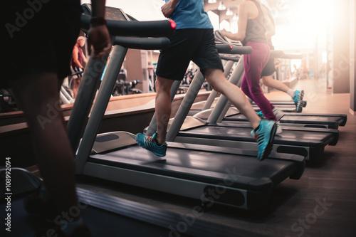 People running in machine treadmill at fitness gym club Fototapeta