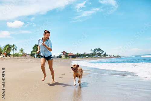 Fototapeta Beautiful Happy Woman Running With Her Dog, Golden Retriever On Wet Sand On The Beach By Sea