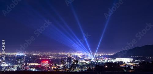 Obraz na plátne Huge spotlight rays over the night panorama of Los Angeles city
