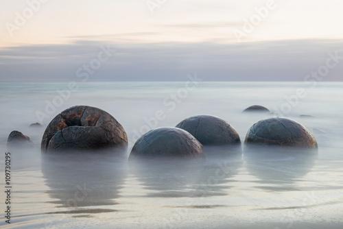 Fotografia Moeraki Boulders on the Koekohe beach, New Zealand during sunrise (long exposure