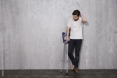 Fotografía Young man in studio with crutches