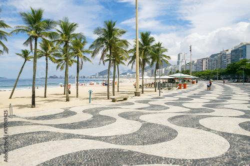 The iconic sidewalk tile pattern of Copacabana Beach curving off into the Rio de Janeiro, Brazil skyline