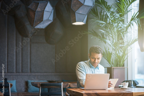 Foto Handsome Arabian guy is making notes from computer