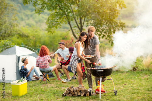 Young female and male couple baking barbecue Fototapeta