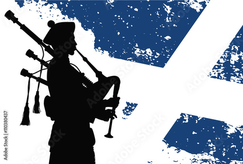 Fotografija Silhouette of a bagpiper with Scottish flag on the background