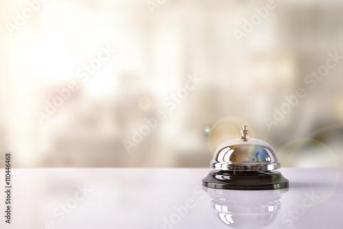 Obraz na plátně Service bell on hotel reception with Hotel background
