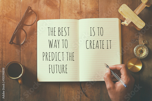 open notebook over wooden table with motivational saying