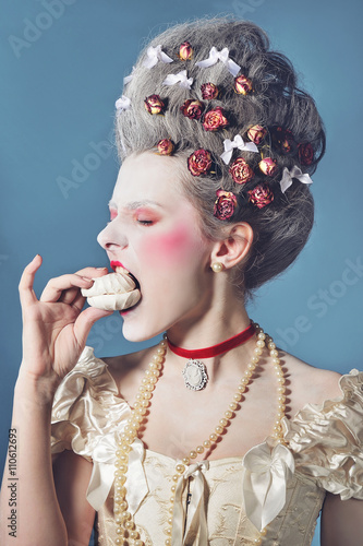 Obraz na płótnie Young woman greedy eating marshmallow in light corset over blue background