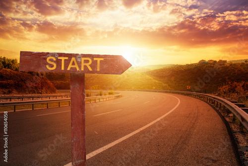 Start Direction on sunset over asphalt road