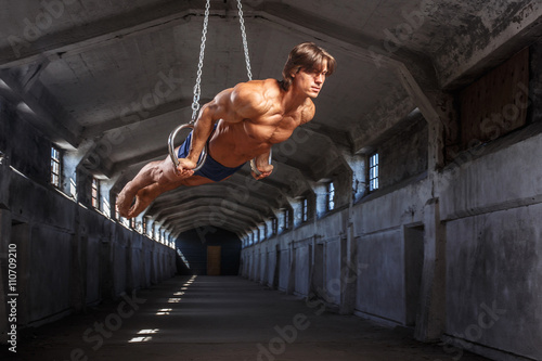 Fotografie, Obraz Muž cvičení ve vzduchu s Gimnàstic kroužky.