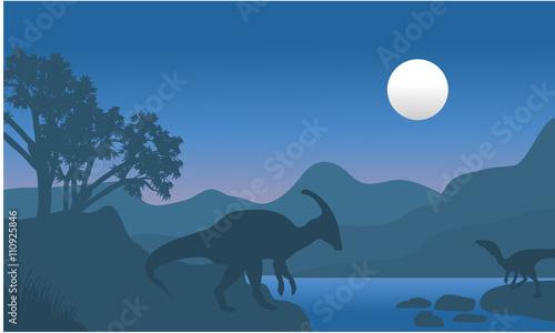 Платно eoraptor and parasaurolophus in river scenery silhouette