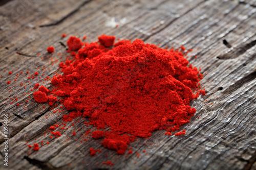 A heap of paprika powder, on wooden surface. Fototapeta