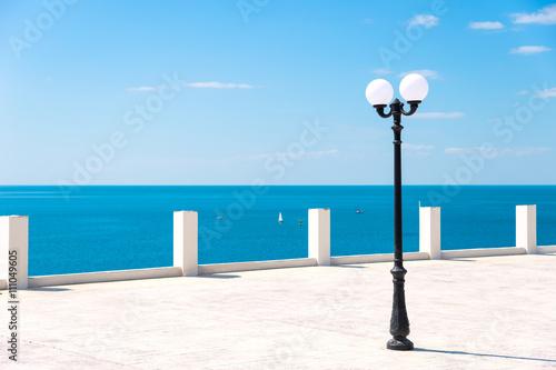 Fototapeta Street lamp on the sea promenade on clear sunny day
