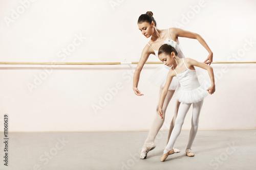 Leinwand Poster Kleine Ballerina tanzt mit Ballettlehrer in Tanzstudio