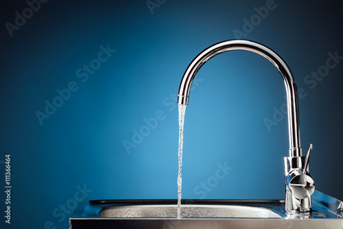 Obraz na plátně mixer tap with flowing water, blue background