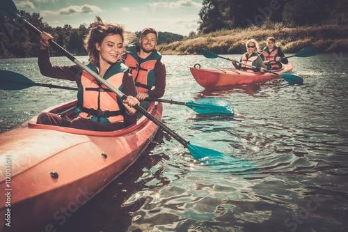 Foto Happy best friends having fun on a kayaks
