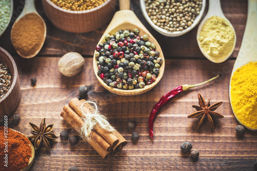 Fotografiet Beautiful colorful spices in wooden spoons and bowls on an old wooden brown table
