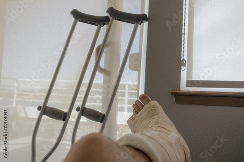 Fotografering Disabled Injured Person With Sprained or Broken Ankle or Foot Sits Inside With Crutches Looking Outside the Sliding Glass Door Window on a Sunny Day