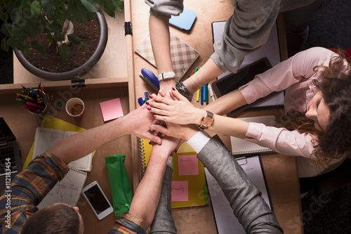 Top view of business people in business suits showing teamwork and unity while working at table in office and discussing certain business issues.